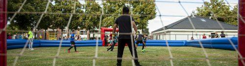 afbeelding voetballende kinderen vanuit de goal gezien